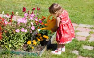 ребенок поливает клумбу